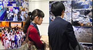 写真を眺める来場者=横浜市中区の日本新聞博物館