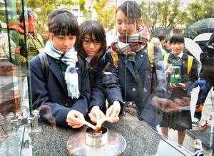 分灯式で、ろうそくに火を移す中学生ら=9日午後、神戸市中央区の東遊園地、水野義則撮影