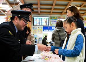 「合格祈願」と書かれた袋に入った滑り止めの砂を手渡す職員ら=奈良市のJR奈良駅