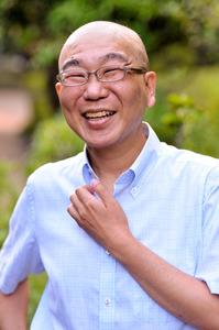 同僚と笑顔で雑談する筆者=昨年8月、東京都中央区築地の朝日新聞東京本社で、瀬戸口翼撮影