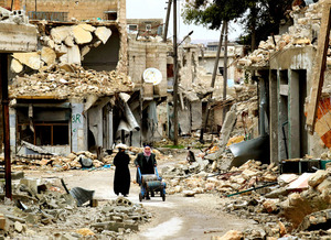 アレッポ東部のハイダリーア地区で、砲撃で激しく破壊された建物の間を歩く人々。ガスや食料などの救援物資を受け取って運んでいた=9日午後、アレッポ、矢木隆晴撮影