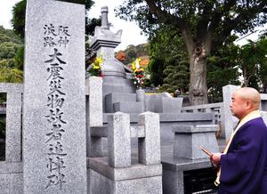 阪神大震災の2年後に全日本仏教会によって建てられた追悼碑。その前に立つ小池弘三貫主=神戸市須磨区の須磨寺