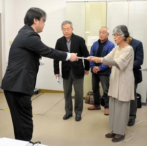 要請・質問書を県担当者に手渡す九つの市民団体の代表の一人、石丸初美さん(右)=県自治会館分館