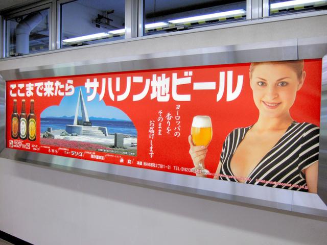 空港にはロシア女性をモデルにした看板も。「ここまで来たら……」というコピーが目を引く=北海道稚内市の稚内空港