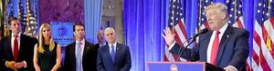 11日、ニューヨークであった記者会見に臨むトランプ次期米大統領。娘のイバンカさん(左から2人目)ら家族や、ペンス次期副大統領(右から2人目)が同席した=AFP時事