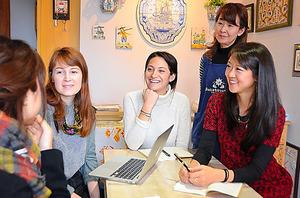 「みなとまちセラミカ工房」で客と話すHBSの学生たちと代表の阿部鳴美さん(右から2人目)。壁には手作りタイルが飾られている=9日、宮城県女川町、長谷川陽子撮影