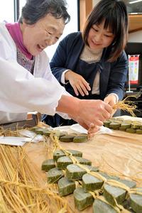 飯舘村の農業の大先輩から凍み餅のわらの編み方を教わる「井戸端会議」の参加者(右)=福島市松川町金沢