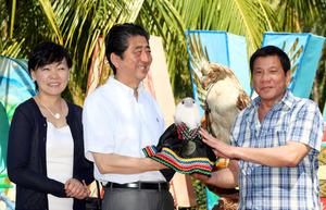 """フィリピンワシの命名式で「サクラ」と名付けられたひなのぬいぐるみをドゥテルテ大統領(右)から贈られる安倍晋三首相(中央)、昭恵夫人。後方は成鳥の<Asajikai sjis=""""剥"""">剝</Asajikai>製(はくせい)=13日午前、フィリピン・ダバオ市内のホテル、飯塚晋一撮影"""