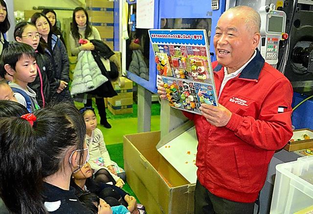 見学に来た親子連れを案内する岩沢善和さん(右)=埼玉県八潮市のイワコー