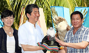 <友好のワシ> フィリピンワシの命名式で「サクラ」と名付けられたひなのぬいぐるみをドゥテルテ大統領(右)から贈られる安倍晋三首相(中央)、昭恵夫人。後方は成鳥の剥製(はくせい)=13日、フィリピン・ダバオ市内のホテル、飯塚晋一撮影