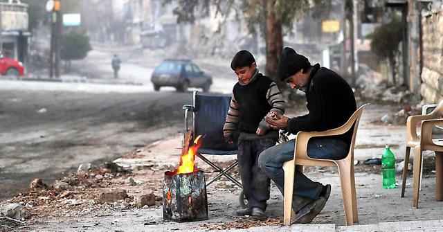 ザブディーヤ地区の自宅に戻ったハルドゥーンさんと息子のアベドくん。電気がないため廃材を燃やして暖をとっている