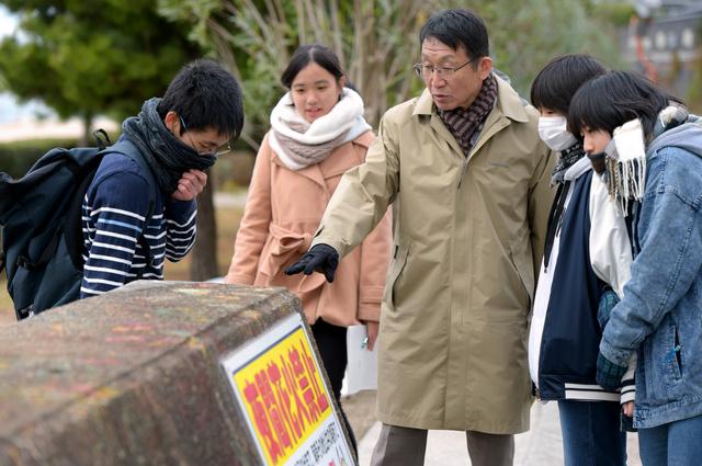 防災マップを作るため、学校周辺を調べる明石高専特命教授の太田敏一さん(中央)と学生たち。堤防の高さなどを測っていた=兵庫県明石市、小林一茂撮影