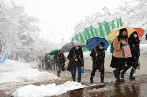 激励ののぼり旗が立つ雪道を会場に向かう受験生=午前8時、長岡市の長岡技術科学大学