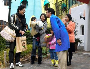 ジブリ美術館の1千万人目の来場者となり、館長らから記念品を贈られる永田晃生さん(左)一家