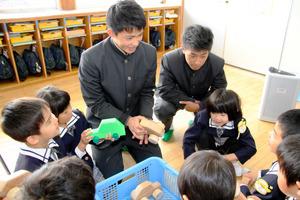 園児らに木製おもちゃの遊び方を説明する島原工業高校生徒=島原市