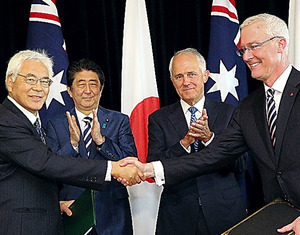 日豪ACSAに関する文書に署名し、握手する草賀純男・駐豪大使(左端)と豪州のブルース・ミラー駐日大使(右端)。立ち会ったターンブル豪首相と安倍晋三首相=14日、シドニー、飯塚晋一撮影