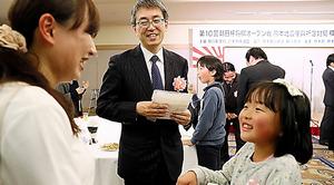 「棋士とのつどい」でファンと交流する羽生善治三冠。熊本市の内藤鈴さん(7)は「がんばってね」と声をかけられ、「羽生さんみたいに強くなりたい」と話した=14日、熊本市、金子淳撮影