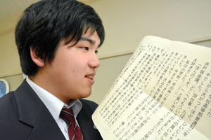 受賞した作文を読み上げる鶴岡涼さん。至近距離に目を近づけないと文字が読めない=福島市の県立盲学校