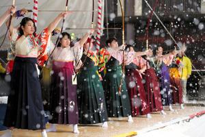 雪が降る中、弓矢を射る新成人たち=15日午前、京都市東山区、佐藤慈子撮影