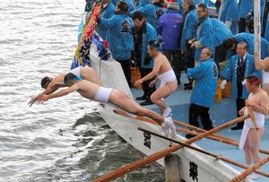 雪が舞う中、次々と川に飛び込む若者たち=豊後高田市の桂川