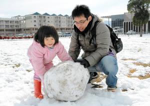 雪だるまを作る親子=山口市