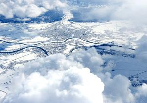 荒天が続く新潟県。三条市付近で高度約8700メートルまで上がると雲間から雪景色がのぞいた=15日午前11時54分、朝日新聞社機から、迫和義撮影