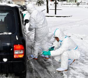 養鶏場から約1キロの地点で、車を消毒する県職員ら=山県市