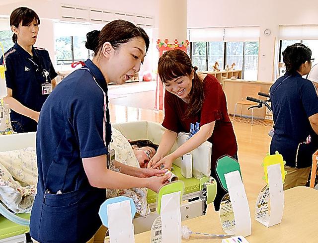 施設の夏祭りで、射的ゲームを楽しむ利用者の横田慶子さん(中央右)と長男の瑛君(3)。「『瑛が社会で生きている』。そんな実感が持てました」=東京都世田谷区の「もみじの家」、池田良撮影
