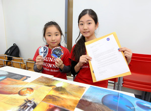 NASAからの手紙とステッカーを持つ生徒たち=今年1月、東京都新宿区