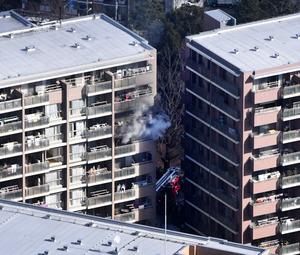 11階部分から煙が上がるマンション=16日午前11時28分、東京都世田谷区千歳台6丁目、朝日新聞社ヘリから、迫和義撮影