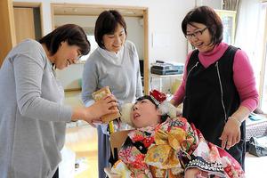 成人式の晴れ着を着た伊勢知那子さん(中央)。東日本大震災のとき、避難所で散髪してくれた美容師が着付けに駆けつけた=宮城県石巻市