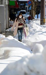 雪に埋もれた歩道を歩く人=宮津市鶴賀