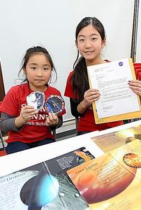 NASAからの手紙とステッカーを持つ生徒=今年1月
