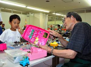 古川耕三さんはおもちゃを丁寧に分解して「手術」をした=長野市