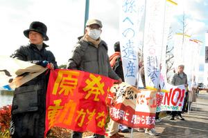審尋前、再稼働反対の横断幕やのぼりを掲げる市民ら=県庁前