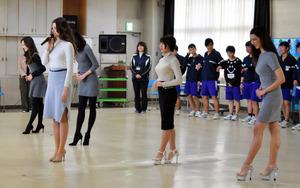 生徒たちに美しいおじぎの仕方を見せる出場者たち=日野中央高等特別支援学校