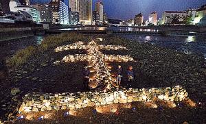 「生」の文字のそばで黙祷する人たち=16日午後5時46分、兵庫県宝塚市、水野義則撮影