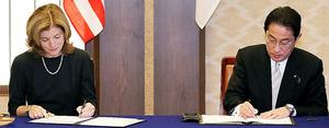 文書に署名する岸田文雄外相(右)とケネディ駐日米大使=16日午後3時9分、東京都港区、関田航撮影