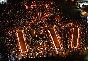 「1995 光 1・17」の文字の周辺で黙とうをする人たち=17日午前5時46分、神戸市中央区の東遊園地、水野義則撮影