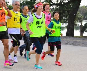 道下美里さん(右端)と伴走用のロープを握り合いジョギングするケネディ大使=2016年10月29日、福岡市の大濠公園