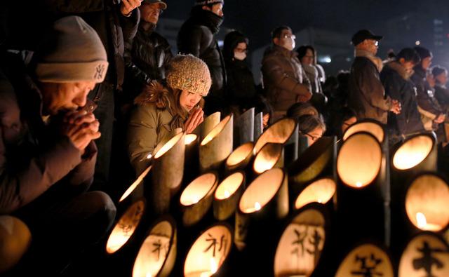 竹灯籠(どうろう)の前で祈りを捧げる人たち=17日午前5時42分、神戸市中央区、細川卓撮影