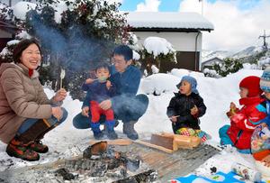 森のようちえんの子どもたちとたき火を囲む伊丹さん一家(左側3人)=智頭町