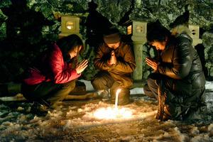 灯籠の前で家族と祈る高嶋さん(中央)=出雲市小境町