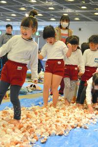 卵の殻の上を歩き裸足の危険性を体感する子どもたち=和歌山市手平2丁目