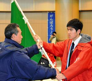 川崎重雄総監督(左)から団旗を受け取る杉田遼河さん=宮崎市旭1丁目