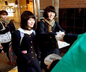 おむすびを受け取る女子生徒たち=JR大分駅北口