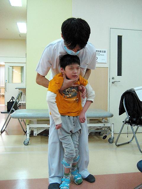 理学療法士に支えられながら歩く世生さん。リハビリは今も続く=大阪市城東区のボバース記念病院