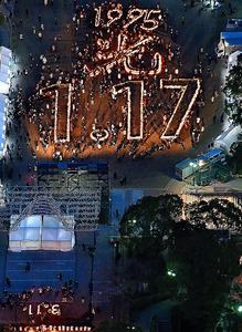 震災の犠牲者を追悼して神戸の街に浮かび上がった「1.17」と「3.11」の文字=17日夕、神戸市中央区