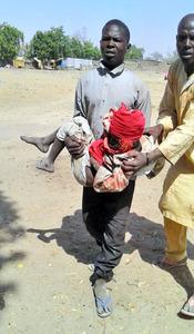 ナイジェリア北東部ボルノ州で17日、避難民キャンプへの誤爆で負傷した子どもを運ぶ男性。国境なき医師団提供=AP
