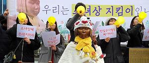 釜山の日本総領事館前に設置された少女像の前で慰安婦問題の日韓合意の破棄などを訴える「少女像を守る会」のメンバーたち=18日午後0時42分、東岡徹撮影